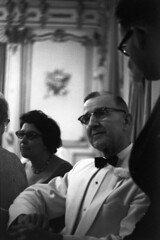 083659 26 (ndpa / s. lundeen, archivist) Tags: people blackandwhite bw woman man men film monochrome guests 35mm glasses blackwhite sitting nick bowtie august tuxedo ballroom 1950s conversation eyeglasses talking corsage seated weddingreception 1959 unidentified formalattire dewolf mingling weddingguests whitetuxedo nickdewolf photographbynickdewolf locationunidentified