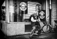 Thug Life. (Mister G.C.) Tags: old city people urban blackandwhite bw man male guy window monochrome deutschland town eyecontact europe sitting image candid streetphotography walkingstick photograph elderly 20mm unposed schwarzweiss streetshot niedersachsen lowersaxony pancakelens primelens sonyalpha mirrorless zonefocusing zonefocus strassenfotografie sel20f28 sonya6000 mistergc