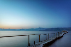 Sunset Across Ionian Sea (A Guy Taking Pictures) Tags: camera blue sunset sea orange sun mountains beach water speed evening pier boat town long exposure flickr sony system greece shutter manual across corfu compact ionian a6000