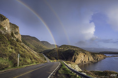 rainbows end at Le Buttereau (Rob Romard) Tags: ocean road mountains clouds rainbow double cabottrail