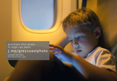 Little boy using tablet computer during flight (creativemarket.photo) Tags: trip travel boy people game window closeup modern plane computer airplane person pc kid cabin portable alone child play little seat board small flight pad bored tired use wireless leisure passenger tablet tab touchscreen touchpad illuminator