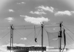 Trapeze artist (Mildred Alpern) Tags: sky blackandwhite net monochrome clouds silhouettes figures trapeze