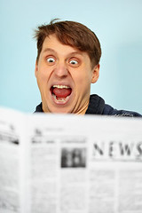 Man shocked - bad news from newspaper (CANDYMICKY) Tags: blue portrait people white news man guy face closeup paper wonder person reading one newspaper pain eyes funny european absurd expression young rage human single surprise shock amazement amusing fury comical frenzy malice astonishment caucasian spite droll dailypaper emotionality