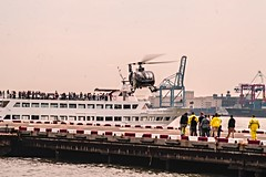 Helicopter Landing At Downtown Manhattan Heliport (Tourist Cruise Boat Passing Heliport) (nrhodesphotos(the_eye_of_the_moment)) Tags: dsc03264160 theeyeofthemoment21gmailcom wwwflickrcomphotostheeyeofthemoment heliport helicopter nyc manhattan brooklyn waterfront eastriver cruiseship boat tourists sightseeing pier people land flying flyingmachine reflections shadows perspective sailing metal glass outdoor hornblowerserenity