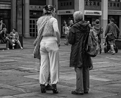 The Height of Fashion (Anne Worner) Tags: street people urban blackandwhite bw woman fashion hair outdoors mono restaurant clothing downtown pavement candid streetphotography hairdo purse backpack raincoat shoulderbag anneworner