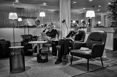Reading Room (Anne Worner) Tags: street people blackandwhite bw woman man orchid coffee wall architecture copenhagen magazine table denmark reading mono book concentration newspaper airport waiting chairs candid travellers lounge streetphotography luggage indoors inside lamps ricohgr waterbottle kastrup glassess concentrated 183mm silverefex anneworner