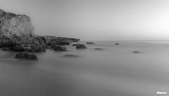 Mediterrani (iEnric.) Tags: costa blancoynegro sol agua playa arena fusion puesta seda rocas horizonte piedras minimalista