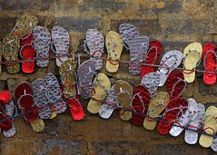 footlose (Rabbania Shirjeel) Tags: street red wall golden shoes hang chappal