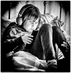 Day 147, 2016, a photo a day. (lizzieisdizzy) Tags: child girl female sitting lounging comfortable concentrating unaware playing reading gaming intense hands crisps headphones listening intently ownworld whiteandblack