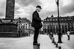 Street - Perched man in the Place Vendome (Franois Escriva) Tags: street light sky people bw sun white man black paris france face hat smart photo noir alone place candid streetphotography olympus nb perched elegant rue blanc omd vendome
