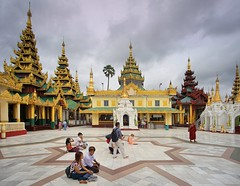 Pilgrims sitting down in front of the Great Dagon Pagoda (Bn) Tags: myanmar birma burma yangon rangoon former capitol street candid monk bikes taxi city six million people buddhist temple botataung pagoda botahtaung gautama buddha hair 2500 years old religions locals 40m high seaport dazzling road car gold kyats umbrella sunshine fietstaxi gate entree hollow destroyed rebuild colonial overwhelmed infrastructure slums pilgrims buddism traffic cycling shwedagonpagoda 2600years 99m cars busy devotees prayer monks golden zedi daw great birds heaven earth