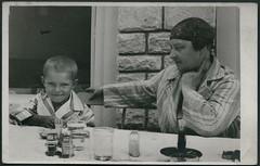 Archiv E814 Bei der Gromutter, Ungarn, 1930er (Hans-Michael Tappen) Tags: boy 1930s child outdoor kind tisch ungarn bub junge enkel feuerzeug wasserglas bademantel ohrring haarnetz 1930er grosmutter archivhansmichaeltappen