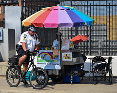 Italian Ice (tim.perdue) Tags: comfest 2016 community festival columbus ohio goodale park outdoor summer party short north victorian village downtown urban city italian ice food cart street candid police officer bicycle cop bike umbrella multicolored colorful rainbow