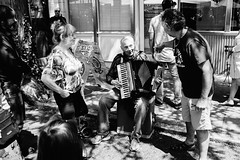 A busker talks to a friend during his set at the Ballard Farmer's Market. Seattle, WA. July 2016. (poopoorama) Tags: ballard dannyngan dannynganphotography fujifilm seattle xseries x100t accordian bw blackandwhite busker farmersmarket market musician people performer street streetphotography washington unitedstates