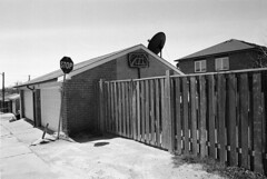 Stop (geowelch) Tags: toronto blackwhite garage fences 35mmfilm laneway urbanlandscape pentaxmx urbanfragments xp2super400 rogersroad plustekopticfilm7400 pentaxtakumara28mm28