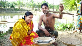Weighing a fish from their pond in Barguna, Bangladesh. Photo by Md Masudur Rahaman, 2012.