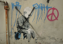 sitting on a wall (mcfcrandall) Tags: boy streetart wall paper graffiti sitting x bomb peacesymbol greywall
