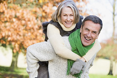 Senior man giving woman piggyback ride (genie_solution) Tags: old autumn woman man tree male fall senior leaves smiling vertical female scarf laughing garden season fun outside outdoors happy countryside clothing healthy 60s couple warm fifties ride adult walk happiness husband tocamera clothes foliage mature together older wife 50s retired piggyback enjoying sixties cosy fit active ethnicity piggybacking caucasian youngatheart atcamera