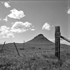 Haystack Butte (JimShootsFilm) Tags: sky blackandwhite 120 film field clouds analog rural america fence mediumformat square landscape blackwhite gate montana butte unitedstates unitedstatesofamerica hill hasselblad pasture squareformat barbedwire powerline analogue prairie agriculture plains prairies backroad ilford barbedwirefence fencepost ilfordpanf gravelroad ruralamerica panf hasselblad500cm gravelroads slowfilm hasselblad500 whitlash bwfp