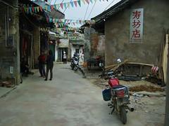 an old street (SM Tham) Tags: china buildings yangshuo streetscene flags motorbike ful guangxi