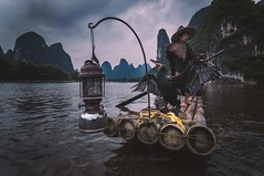 Ready for action (Syahrel Azha Hashim) Tags: china travel light vacation portrait holiday mountains detail bird water colors hat clouds river cormorants fishing fisherman nikon colorful dof expression guilin getaway unique traditional details chinese paddle naturallight oldman bamboo tokina portraiture elder handheld editorial lantern shallow moment simple dramaticsky paddling iconic 11mm conventional oneperson bambooraft ultrawideangle colorimage syahrel