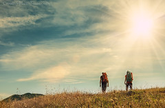 Two mountain travelers with backpacks under blue sky (CreativePhotoTeam.com) Tags: trip travel blue summer portrait sky people italy cloud sun mountain alps green tourism nature beautiful grass sport trekking way landscape person freedom climb healthy scenery view outdoor hiking weekend scenic lifestyle peak sunny tourist hike adventure direction walker journey valley backpack leisure hiker wilderness activity backpacker idyllic active traveler