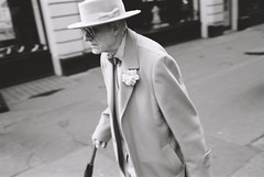 Man with hat, West End (fabiolug) Tags: street leica people blackandwhite bw man london film hat umbrella walking glasses blackwhite candid streetphotography bowtie rangefinder suit fujifilm elegant m6 westend gentleman acros dapper leicam6 londoners candidphotography londonist acros100 theatreland leicam6ttl fujifilmneopanacros100 fujifilmacros100 fimphotography leicam6ttl072 believeinfilm georgeskeggs vision:outdoor=0863