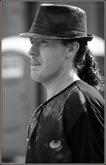 Hat man (* RICHARD M) Tags: street portrait monochrome tongue liverpool portraits mono blackwhite candid hats curls curly portraiture ponytail candids curlyhair trilby catseye merseyside pullingtongues eberlestreet liverpoolpride liverpoolgaypride