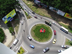The Cars At The Roundabout Go Round and Round... (thienzieyung) Tags: city trees cars lines buildings circle landscape traffic loop centre roundabout sunny scene replica vehicles busy hibiscus queue malaysia round arrows kotakinabalu intersection sabah congestion lanes perkasa trafficcircle bustling thienzieyung