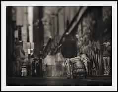 laneway figures III (Andrew C Wallace) Tags: city blackandwhite bw streetart blur sepia lensbaby ir graffiti photographer dof australia melbourne olympus victoria tourists pedestrians infrared cbd laneway suitcase hosierlane shallowdof tiltshift nd400 m43 720nm nikon50mmf14 microfourthirds tilttransformer olympusomdem5