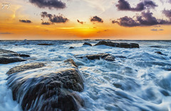 Fire in the sky and Milk on the rocks :) (Yogendra174) Tags: sunset fire orange blue milky smoothwater tides sea sky clouds rocks flow flowingwater wideangle ultrawide 10mm