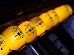 Kirin Yellow (David Panevin) Tags: street yellow japan night lights evening bokeh olympus  lanterns shops osaka namba kansai omd em1  urbanfragments bokehlicious davidpanevin mzuikodigitaled75mmf18