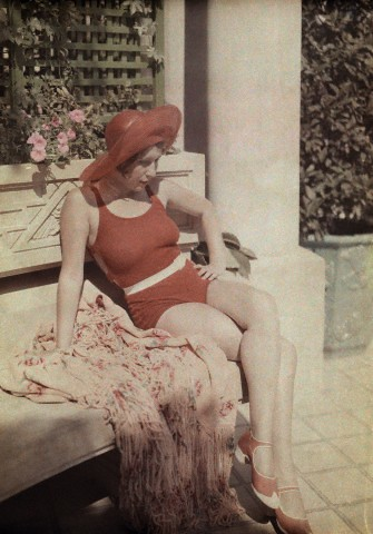 1936 - A woman wearing a red bathing suit and hat sits on a bench (Bucharest)