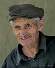 SERBIAN COUNTRYMAN IN RSOVCI (SERBIA, BOR, PIROT, RSOVCI) (KAROLOS TRIVIZAS) Tags: portrait man smile face look hat person eyes head expression character serbia highlander farmer glimpse glance bor flatcap physiognomy pirot countryman rsovci