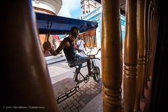 Bike-taxi driver in Calle Obispo, Havana, Cuba (Catherine Gidzinska and Simon Gidzinski/grainconno) Tags: 2016 adventure city cuba gadventures havana holidays lahabana travel people taxi bike rickshaw man cuban cubano calleobispo candid