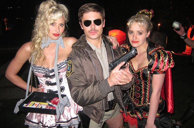 Zac Efron is ultra-serious as a retro cop with a big gun as he poses with duo Aly & AJ, both in racy costumes.