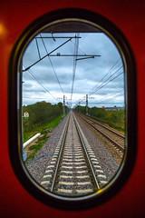 Train window (阿戈卫AGUI) Tags: travel trees windows red cloud grass speed cloudy trains powerlines poles railways