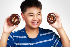 Little asian boy holding a chocolate donuts (Patrick Foto ;)) Tags: boy portrait people food white black smile face childhood cake closeup breakfast youth asian dessert fun thailand happy one kid healthy holding junk funny child little sweet eating chocolate background fat young adorable lifestyle happiness sugar delicious eat health donuts donut thai pastry hungry diet temptation obesity isolated obese overweight