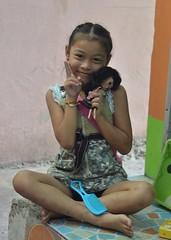 cute girl with doll (the foreign photographer - ) Tags: cute girl sign portraits thailand nikon doll sitting peace cross bangkok lard bang legged bua khlong bangkhen d3200 phrao