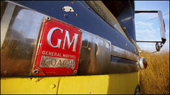 The old GM motor coach (Eric Flexyourhead) Tags: old city blue urban canada detail bus dusty yellow vintage emblem coach gm shiny bc market britishcolumbia dirty richmond chrome badge nightmarket 169 fragment motorcoach generalmotors richmondnightmarket gmcoach panasoniclumix714mmf40 olympusem5