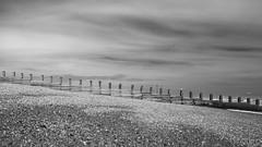 Groyne (Ambra Marras) Tags: wood uk light shadow sea england sky white black beach water monochrome horizontal clouds contrast waves sediment eastbourne groyne sandrock