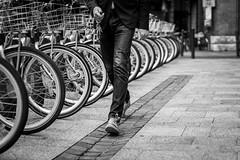 Walking through (Go-tea) Tags: street city urban bw white man black france canon keys outside eos 50mm blackwhite shoes alone floor outdoor walk parking wheels bikes line bicycles toulouse bnw poeple 100d
