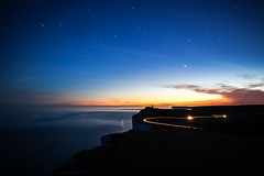 (drfugo) Tags: blue sea sky orange beach water grass night clouds stars hotel chalk brighton waves glow dusk cliffs eastbourne newhaven lighttrails bluehour scrub whitecliffs seaford southdowns beachyhead southdownsway startrail belletout sigma28mmf18exdg canon5dmkii