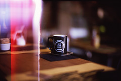 First Frame (VIII) - Sunday Morning (NyYankee) Tags: sunlight film cup coffee table 50mm bokeh f10 lightleak noctilux caf leicam6 kodakelitechrome100 reversalfilm kodakeb3 noctilux50mmf10