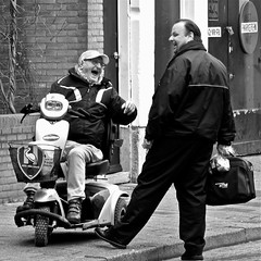 An enjoyable encounter (Akbar Simonse) Tags: street urban bw pet holland men blancoynegro netherlands monochrome laughing square fun glasses zwartwit nederland streetphotography scooter denhaag cap haag lachen ado thehague bril streetshot straat mannen scootmobiel mobilityscooter