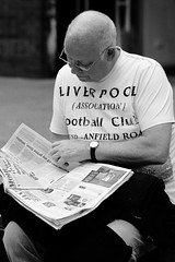 The morning after (cathbooton) Tags: street city morning blackandwhite news sunshine club bench reading glasses fan newspaper football candid may 100mm final win canoneos gent winners supporters anfield liverpoolfc canonusers