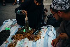 Shopping between prayers (Dunez Photography & Design) Tags: woman beads fuji rosary customer fujifilm niqab merchant saudiarabia seller burqa makkah dhikr xe2