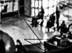 Travelers on the Same Plane (Anne Worner) Tags: people blackandwhite bw chicago geometric architecture lensbaby dark walking mono airport glow bokeh wheelchair curves highcontrast olympus luggage ohare traveller f16 riding backpack underneath concourseb concoursebtoc em5 anneworner omdem5 velvet56
