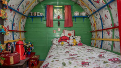 The interior of a horse-drawn bowtop gypsy caravan made into a Snoopy-themed child's bedroom (Anguskirk) Tags: uk england mugs bed interior eu pillows cups snoopy gb horsedrawn gypsy cushions romany childsbedroom bowtopcaravan canvascovered paintedkettle