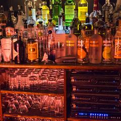 Bottles and Glasses and HDMI MATRIX SWITCHER (wwward0) Tags: nyc red newyork glass bar us bottle technology unitedstates manhattan lounge indoor cc electronics liquors wwward0